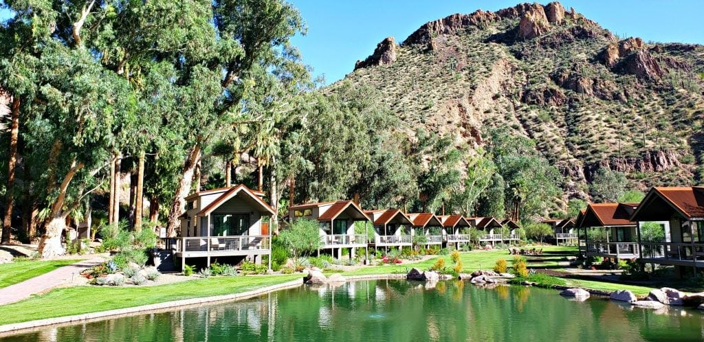 Granite mountain rises up behind oasis of palm trees, pond and new, minimalistically styled cabins