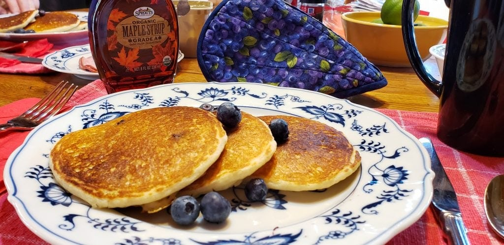 Blueberry pancakes on plate with Canadian maple syrup behind