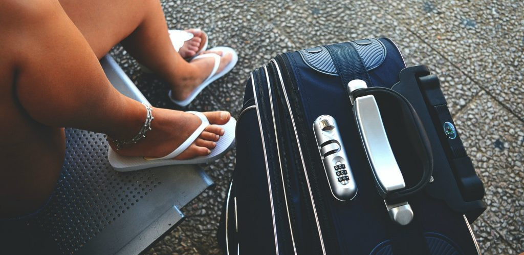 photo from above shows close up of safety locks on navy suitcase - one of the best lightweight luggage for international traveling - the manicured toes of the traveler show on her white flipflops