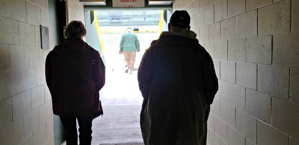 silhouettes of man and women tourists going into stadium from dark hallway 1. Lambeau Field Green Bay Wisconsin Tops the List of Things to See In Green Bay