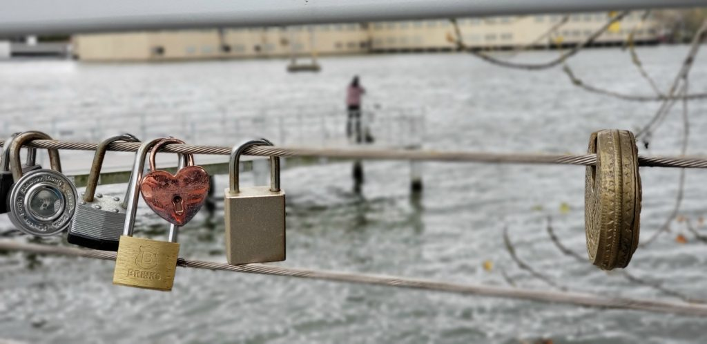 heart-shaped padlock and MasterLock padlocks hang from the cable below the handrails at De Pere Riverwalk, one of the Things to do in Green Bay Wisconsin