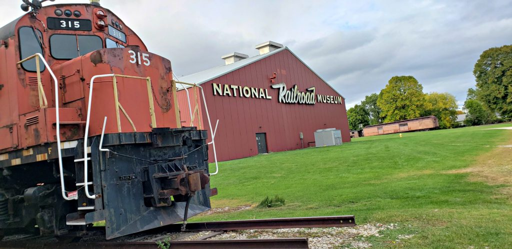 """red locomotive in the foreground, train barn in background with sign reading """"NAtional Trailroad Museum,"""" which is One of the Best Green Bay WI Attractions"""