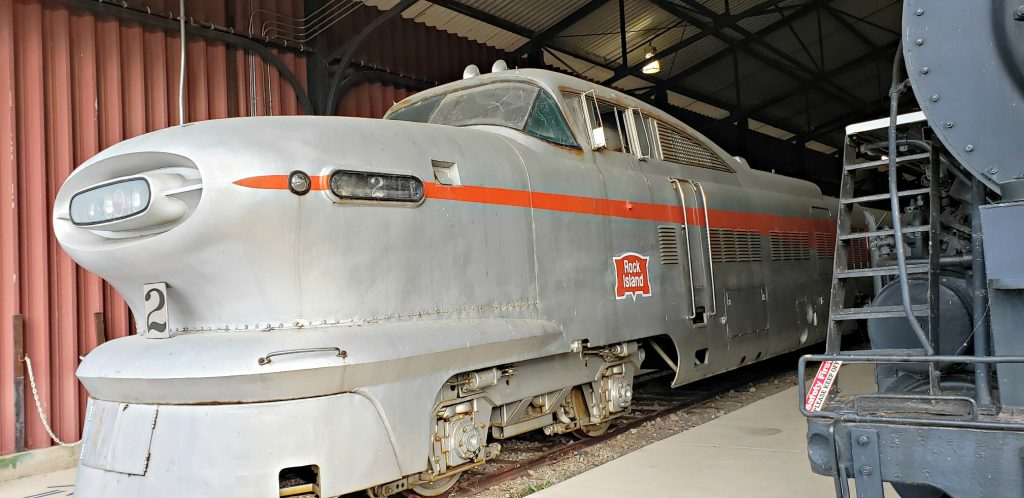 A locomotive with long, greyhound-like nose and aerospace-like small windows sits on track in museum one of the best things to do in Green Bay WI