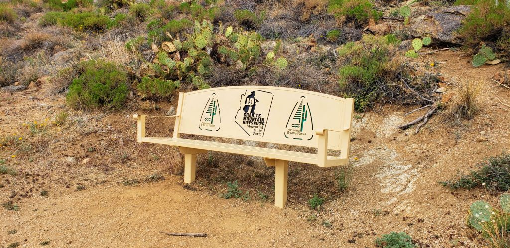 benchh in the desert with prickly pear catus behind. The number 19 is cut out of the metal chair back at Granite Mountain Hotshots Memorial Sate Park