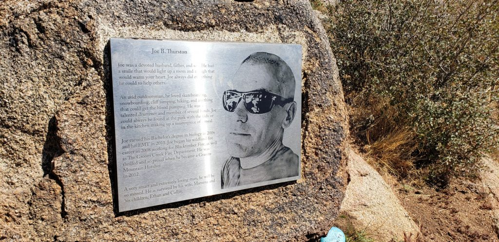 Brushed stainless steel marker with image of Granit Mountain hotshot engraved on it, mounted to granite boulder