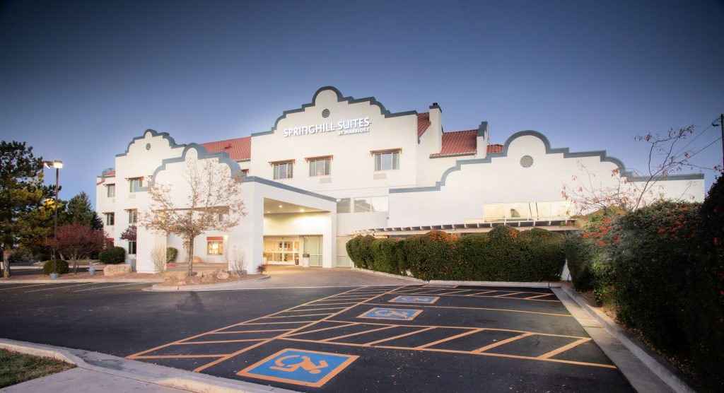 Hotel with Santa Fe style architecture, red tile rood, cream adobe-like walls