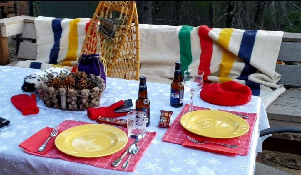 Outdoor table set with snowflake table cloth, red napkins with Canadian flags, Labatt's beer, Hudson Bay blanket, snowshoes and Croen Royal whiskey in purple flannel bag
