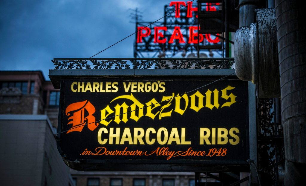 """sign reading """"Charlie Vergos Rendezvous Restaurant """" with neon of the Peabody Hotel behind - can see brick buildings of downtown Memphis"""