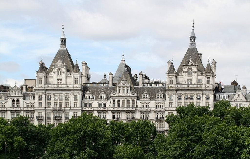a white long building modeled after a French chateau is where the Royal Horseguards Hotel is located