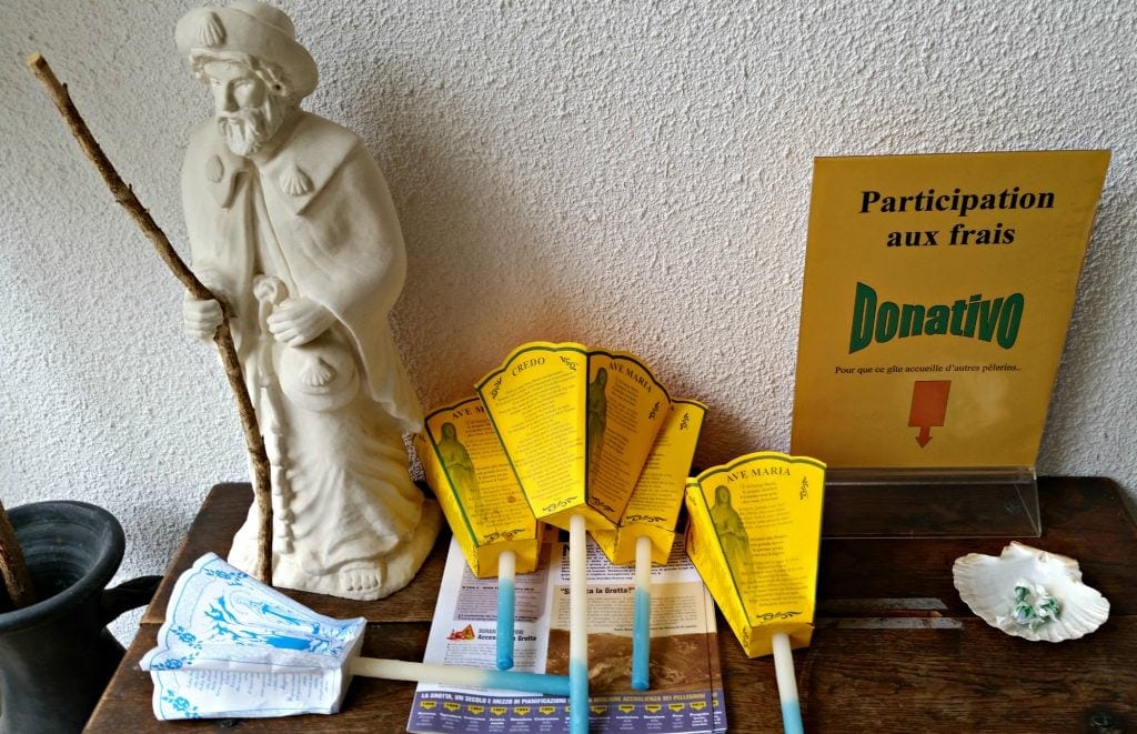statue of st james, candles with paper cone to catch dripping wax and a donation box on wood table