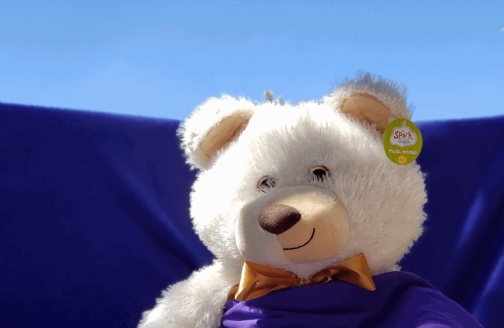 "Plush stuffed polar bear toy sits in ""field of purple flowers"" which is really a purple blanket"
