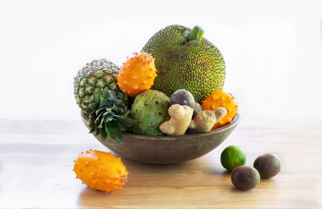 very large wooden bowl filled with rare exotic fruits including kiwano melon, passion fruit, jackfruit, pineapple, cherimoya and more