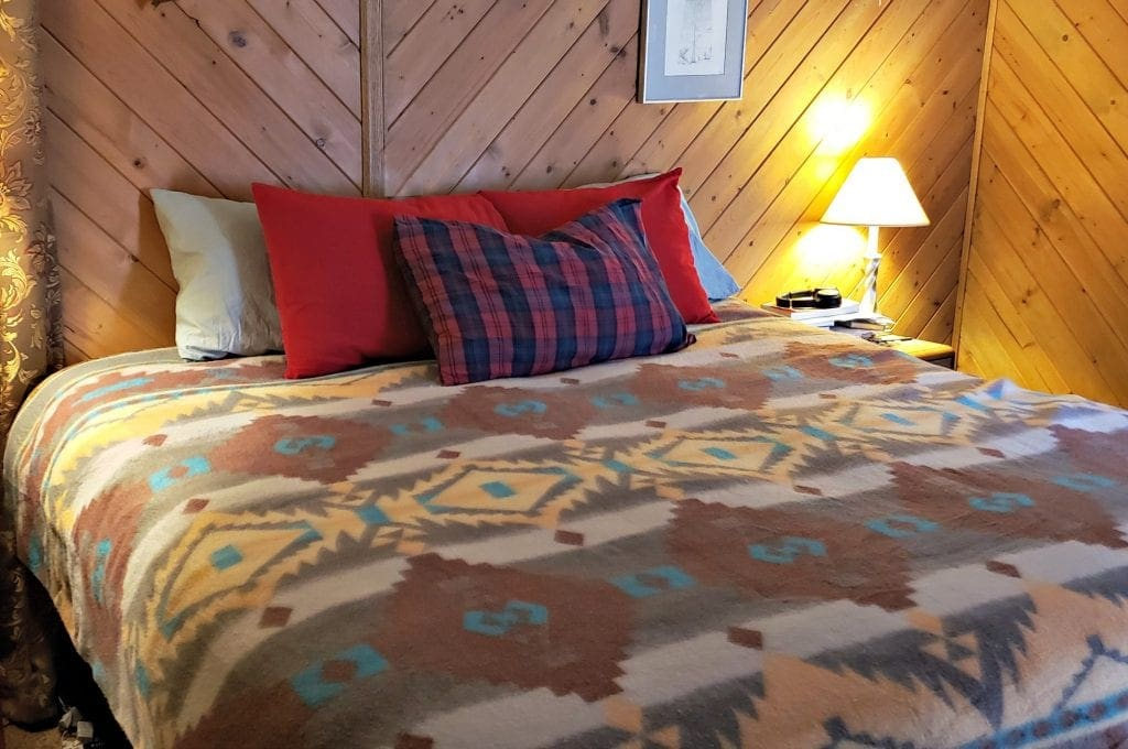 Bedroom with cedar wood walls - bed has Native design bedspread - pillow with red plaid flannel