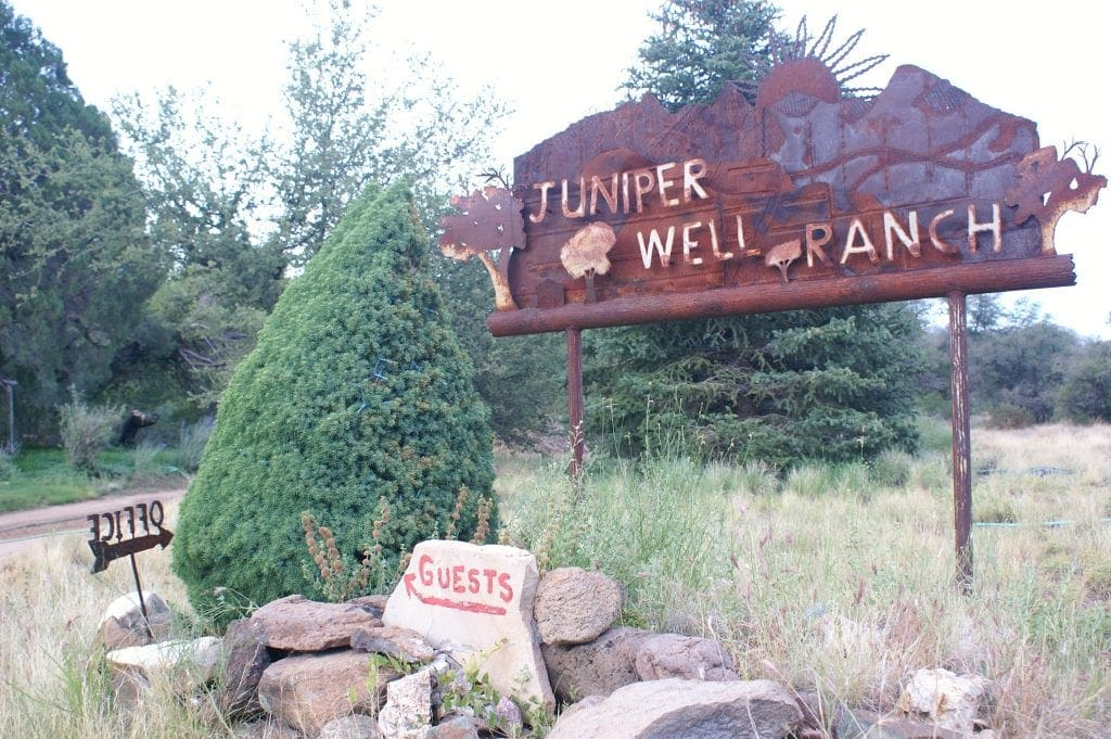 """rusty sign that reads """"Juniper Well Ranch"""" with rocks and evergreen trees at ranch getaway"""