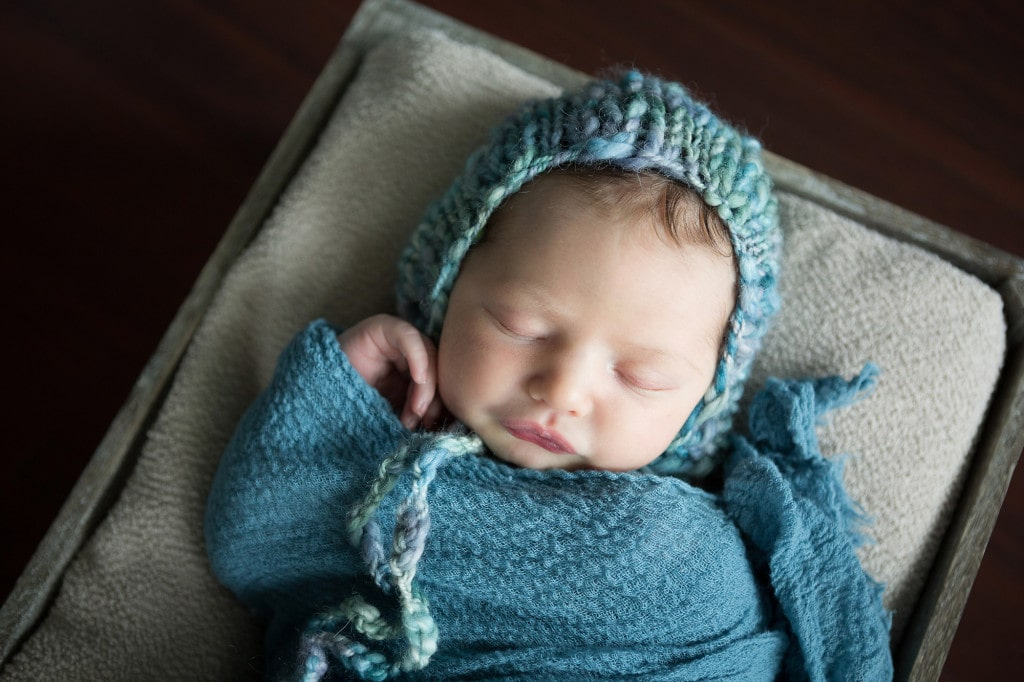 newborn in teal hat and wrap during photo session at home