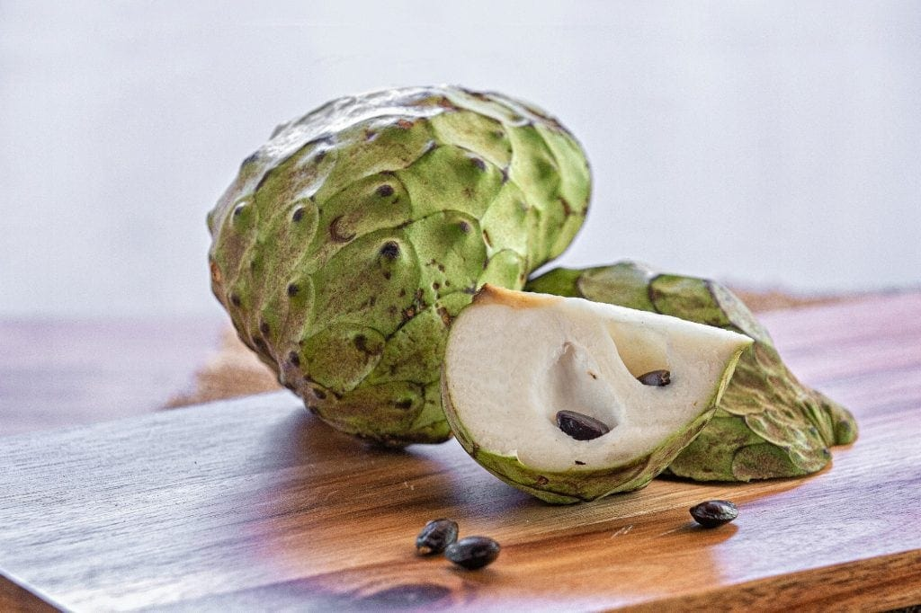 quartered cherimoya lays in front of whole cherimoya revealing white interior and dark brown seeds