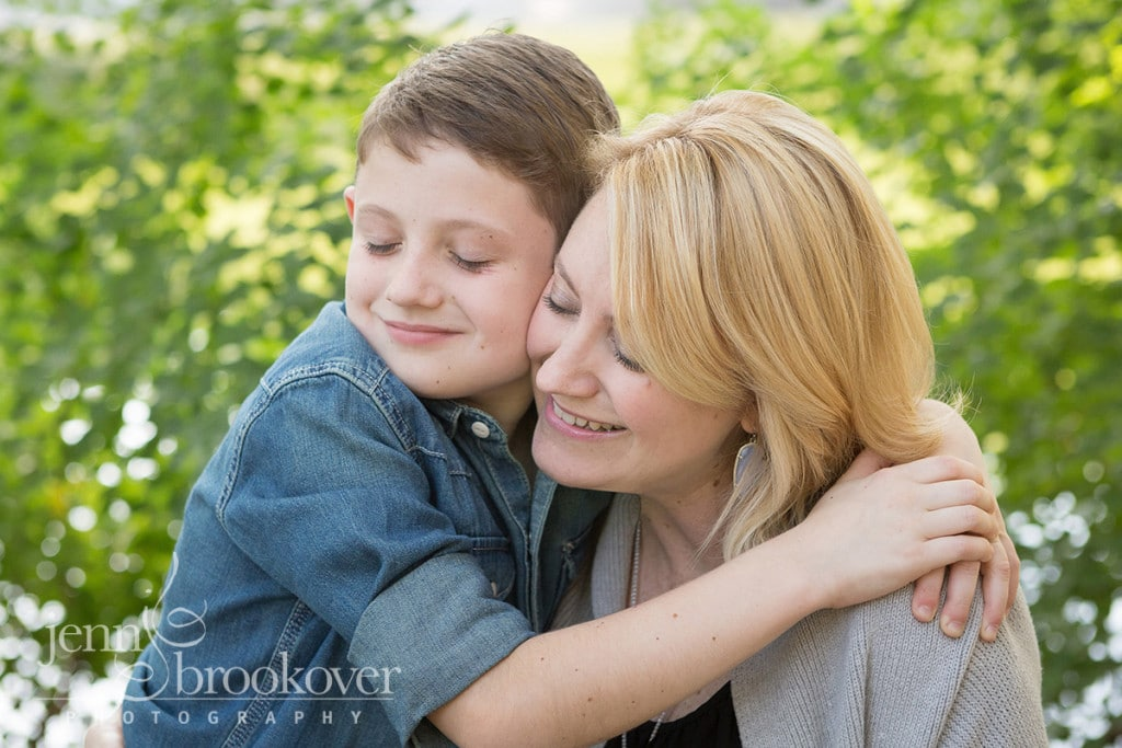 mom and son smiling and snuggling in the park at Denman Estates