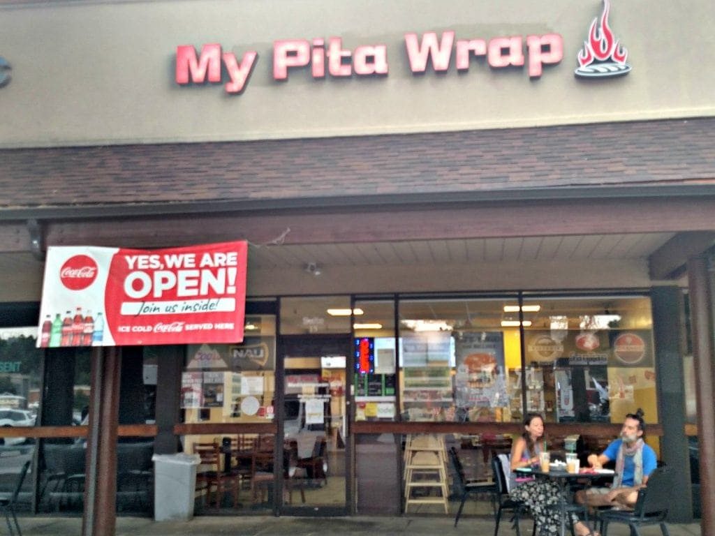 """Front of restaurant with banner that reads """"We're open"""" at one of the best places to eat in Flagstaff AZ"""
