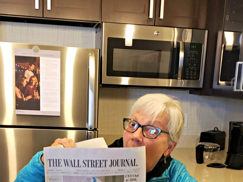 Arizona travel writer Stacey Wittig reads complimentary Wall St Journal in her suite with stainless steel refrigerator, microwave and coffee maker behind her at The Residence Inn Flagstaff