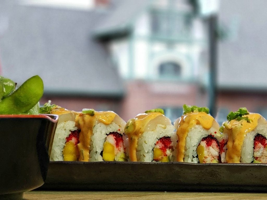 Sushi roll in long black black plate - Flagstaff historic depot can be seen through window