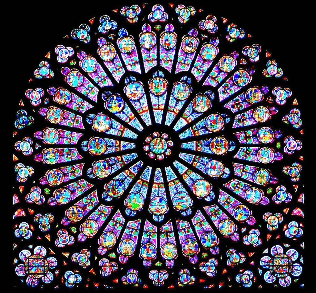 Huge round window full of blue and purple glass depicting Bible stories that cannot be discerned from this distance is silhouetted against the dark, black walls of the cathedral's interior walls makes this a great piece for experiencing God in art