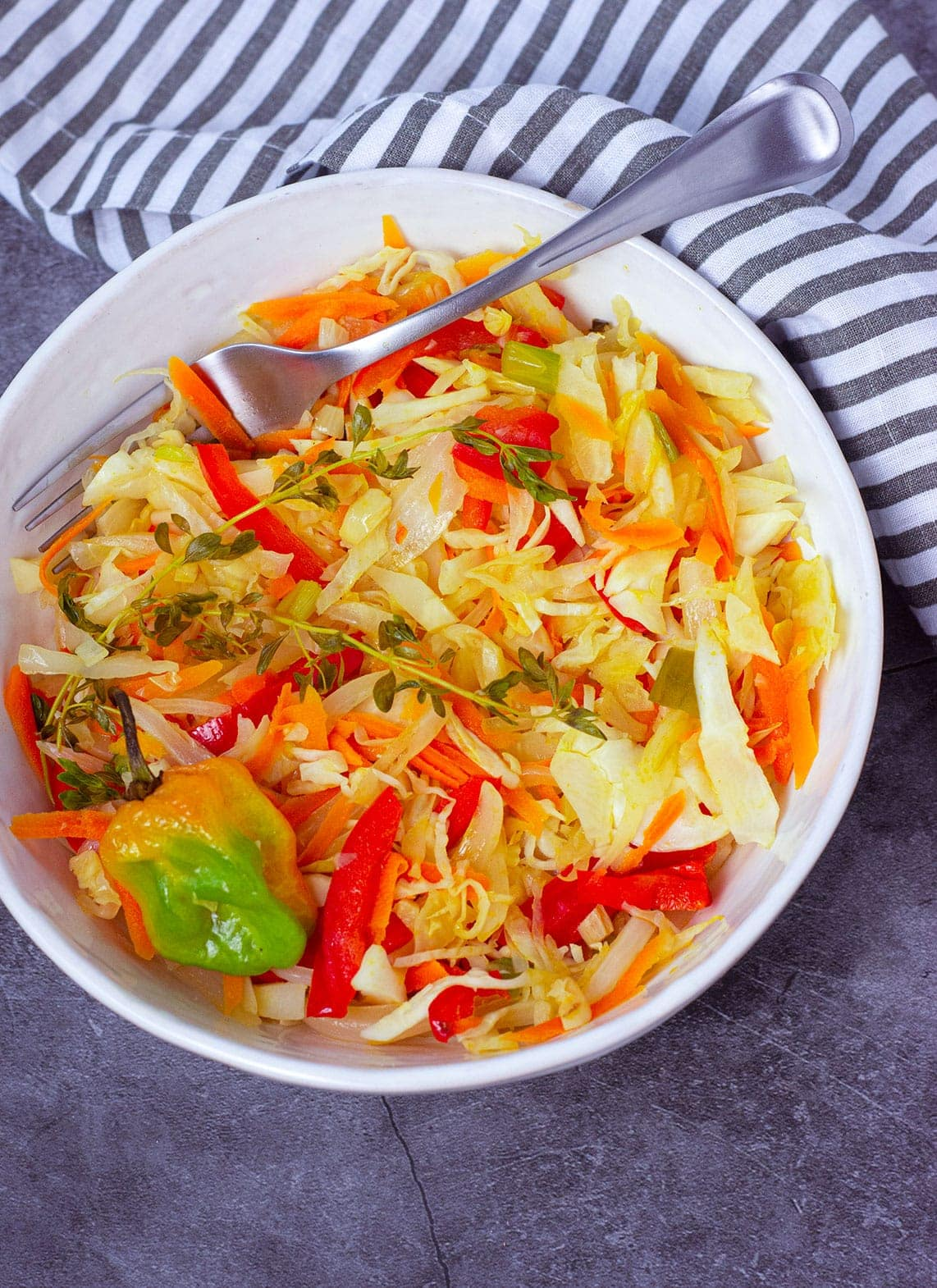 Jamaican Steamed Cabbage overlay in a white bowl on a grey background