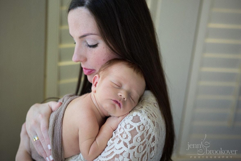 newborn over mom's shoulder in nursery at home in San Antonio
