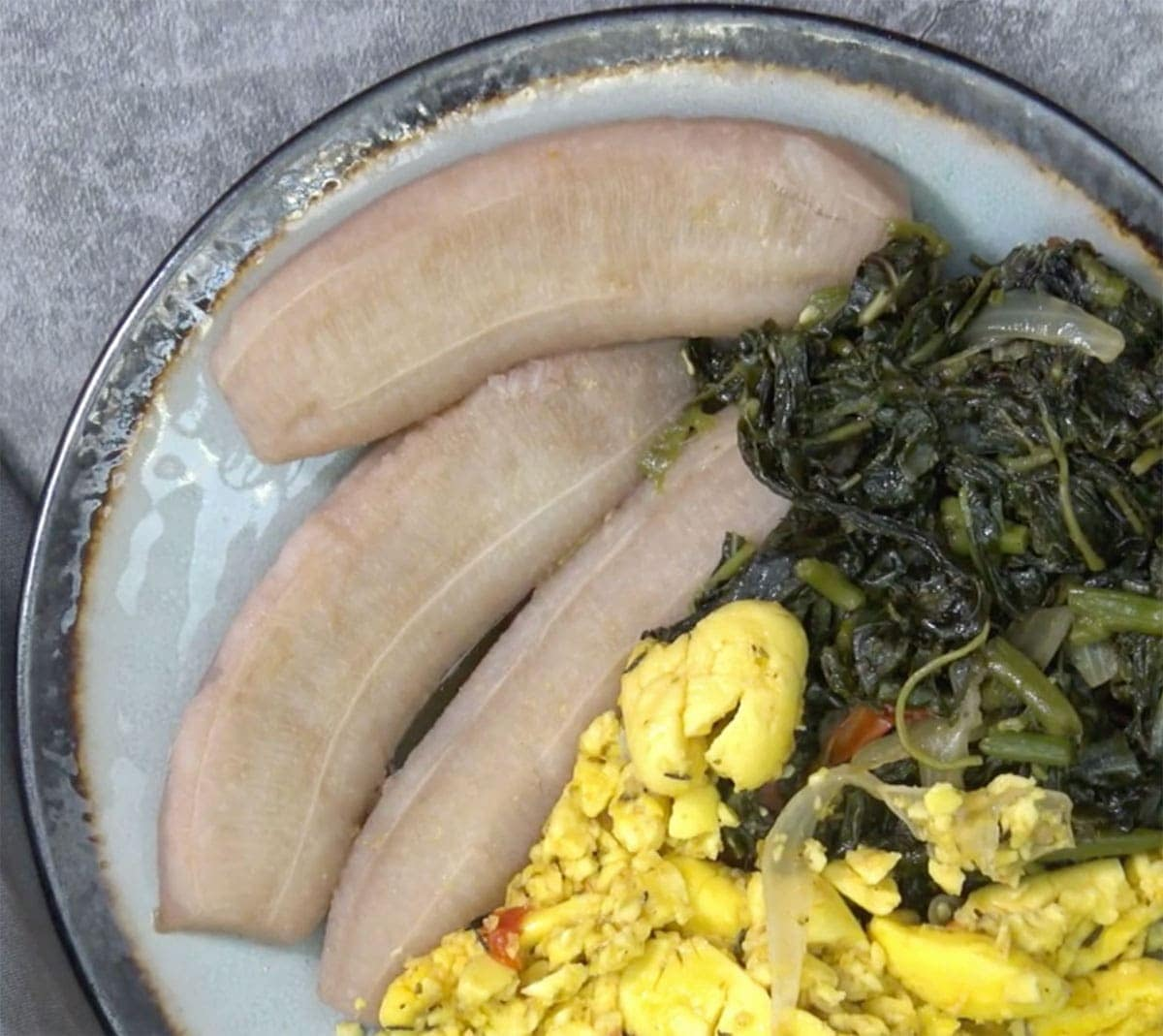 boiled green banana on a blue plate with ackee and callaloo on a grey background