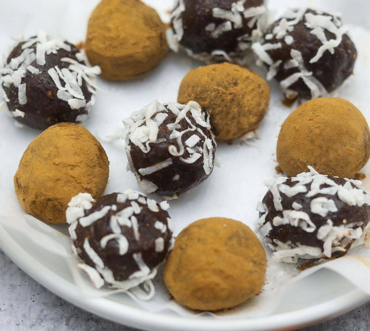 carob truffles in a white plate, close up view