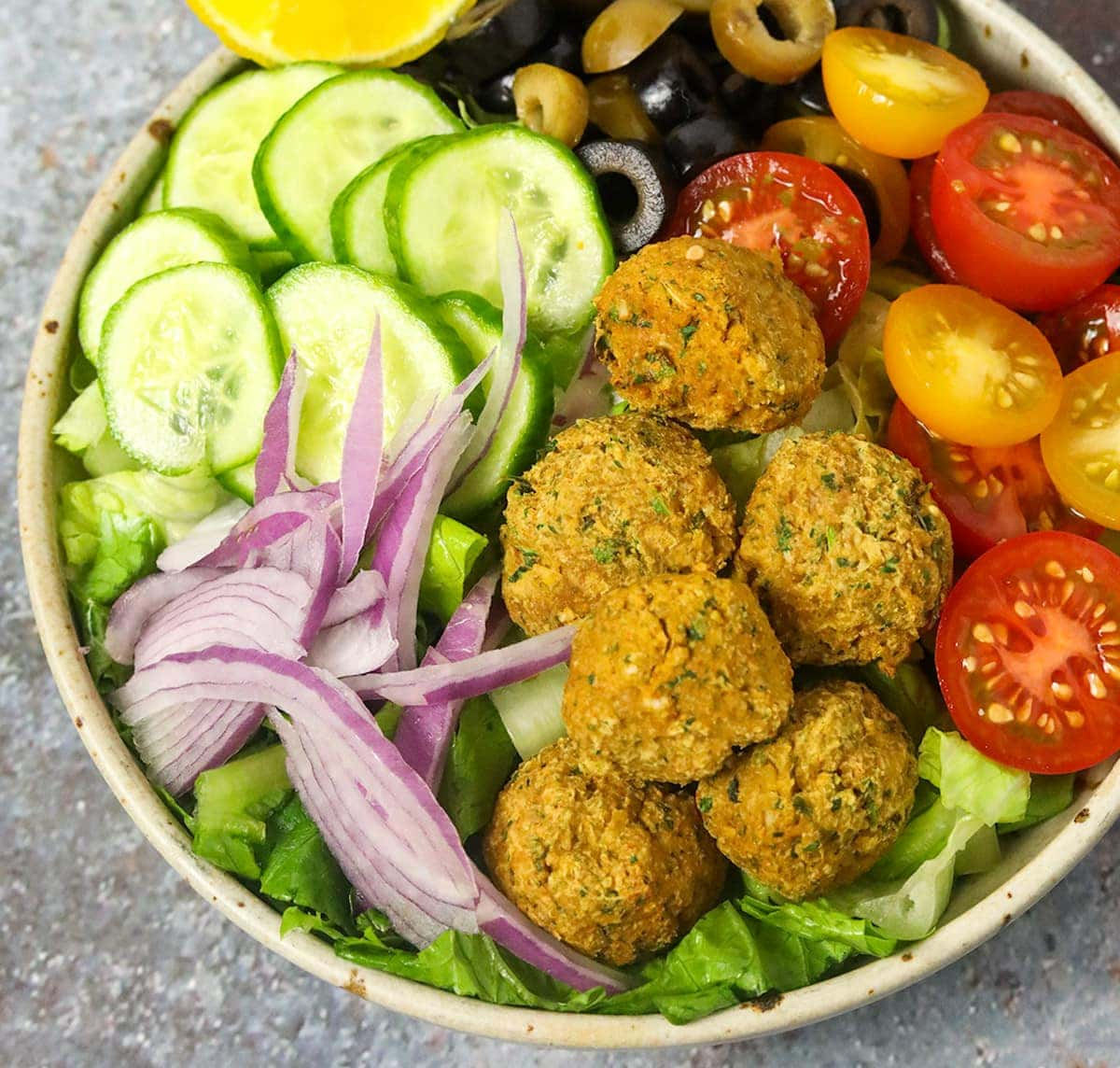 Close view of falafel salad in a bowl on a grey background