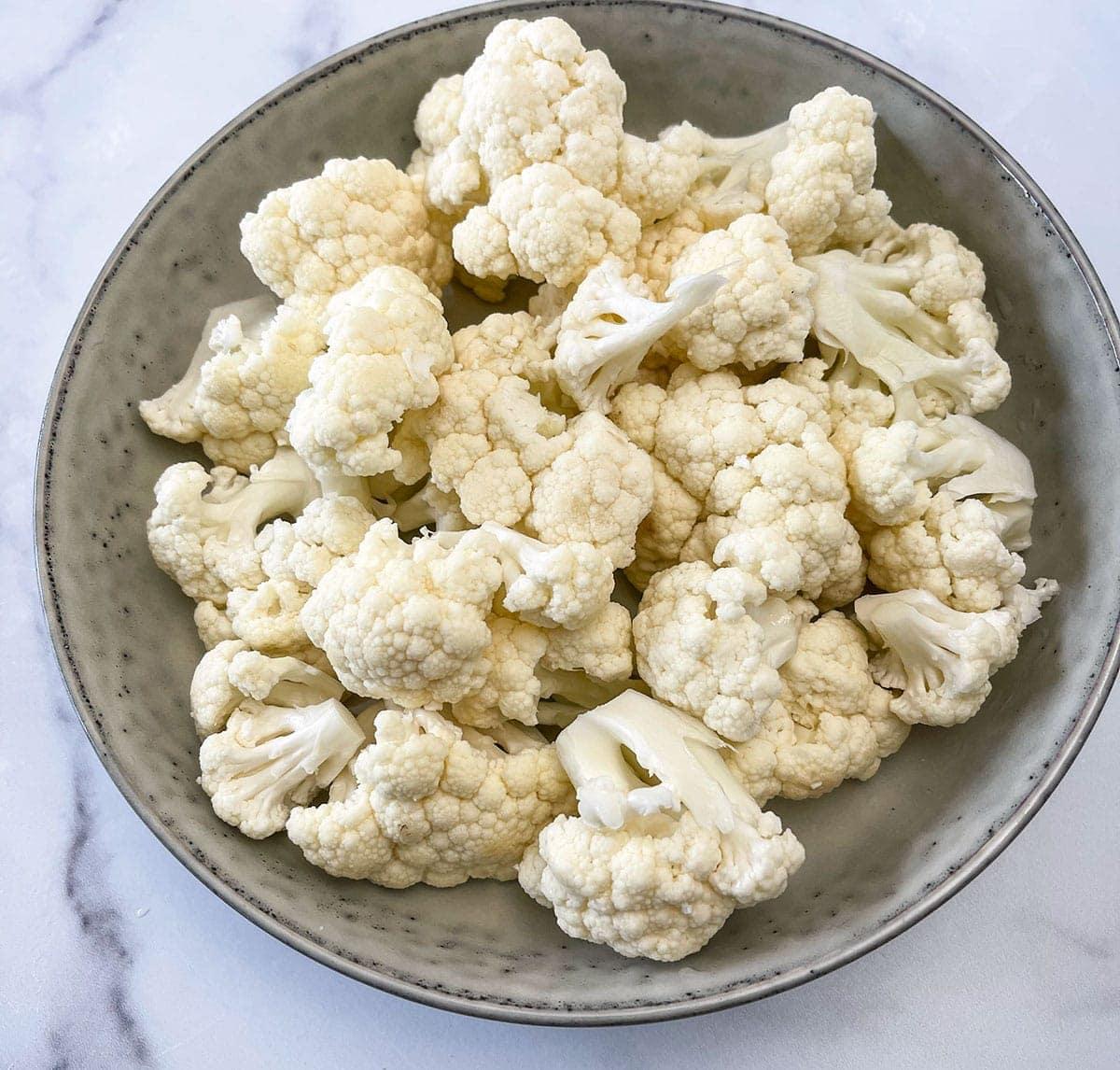 cut cauliflower florets in a beige bowl on a white background