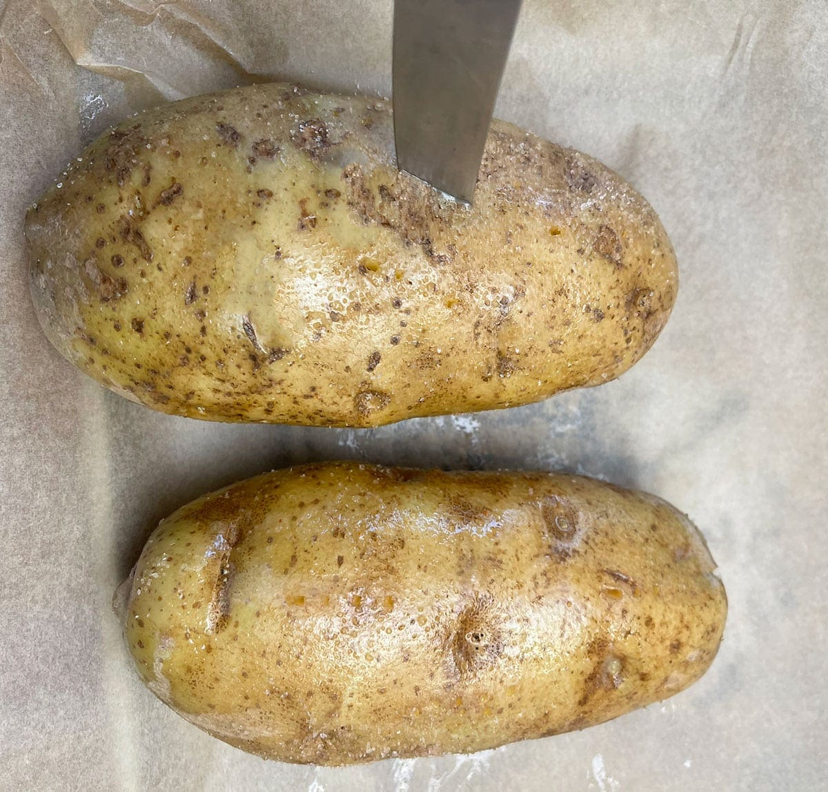 whole baked potato pierced with knife