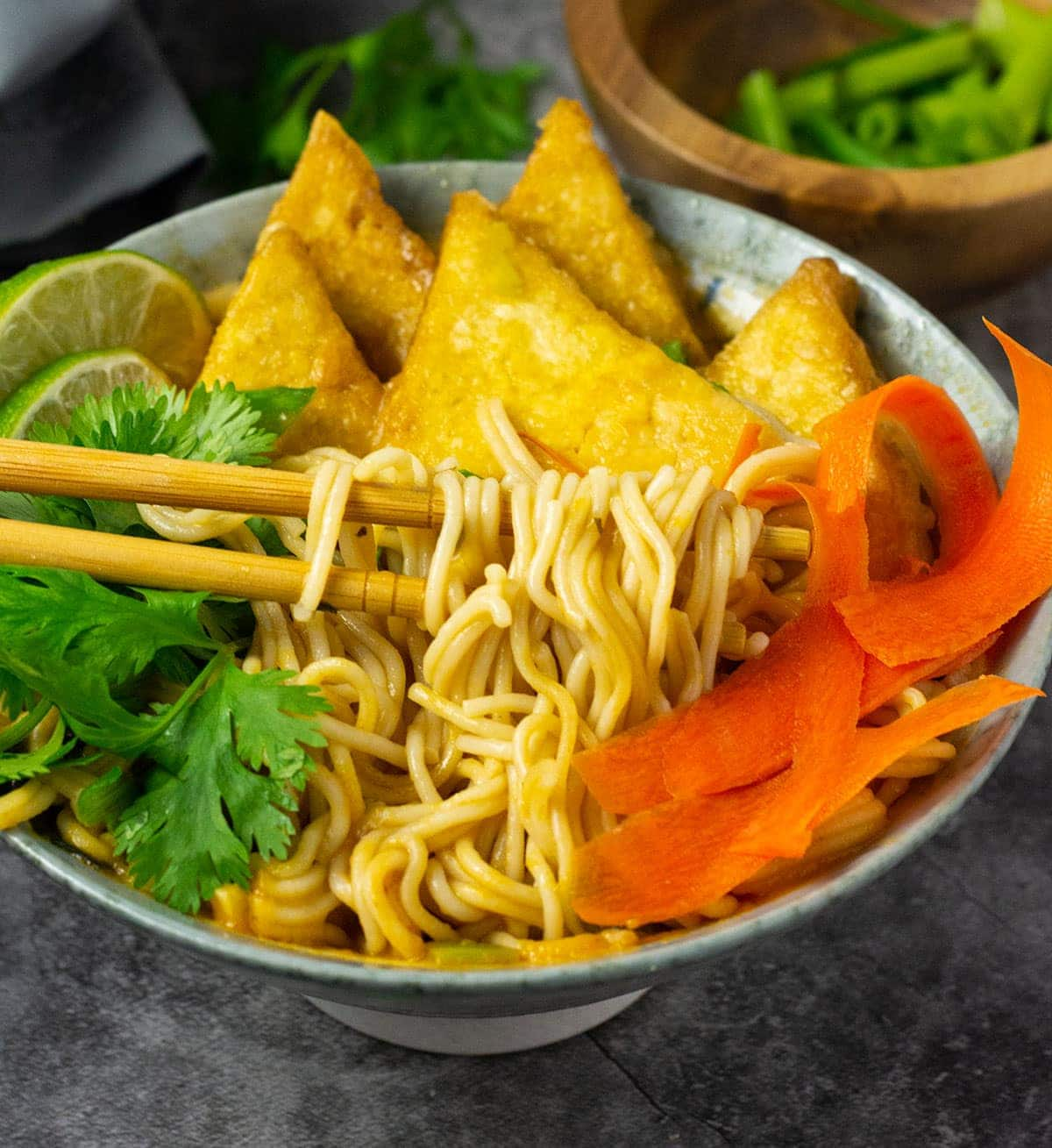 vegan ramen soup noodles in a bowl, being held by chopsticks on grey background