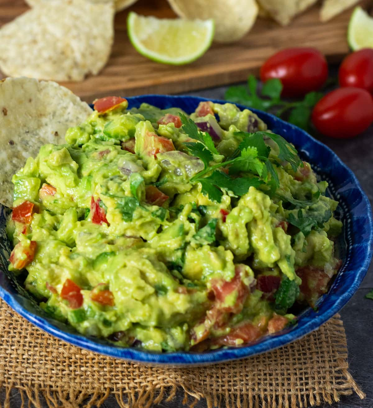 Loaded guacamole recipe with cilantro leaves, tortilla chips on a grey background with cutting board and extra ingredients in the background