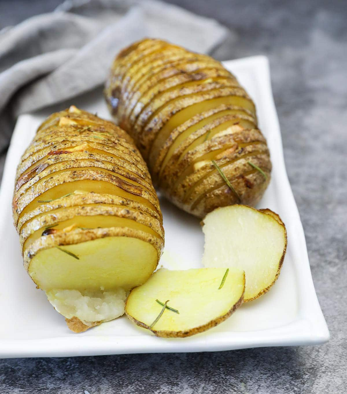 hasselback potatoes, cooked , served on white plate