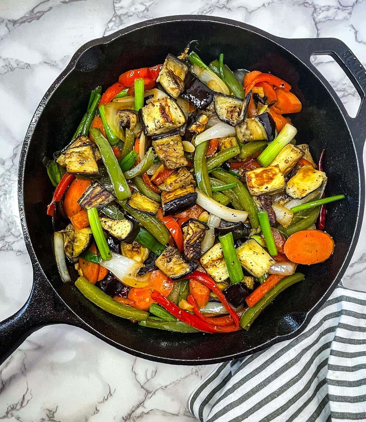 eggplant stir fry in a cast iron skillet on a white marbled background