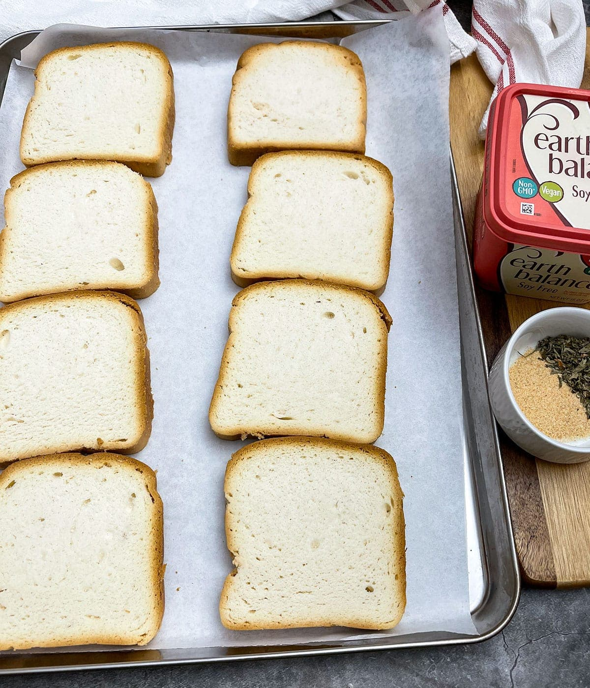 Texas toast slices on baking sheet with seasoning and vegan butter