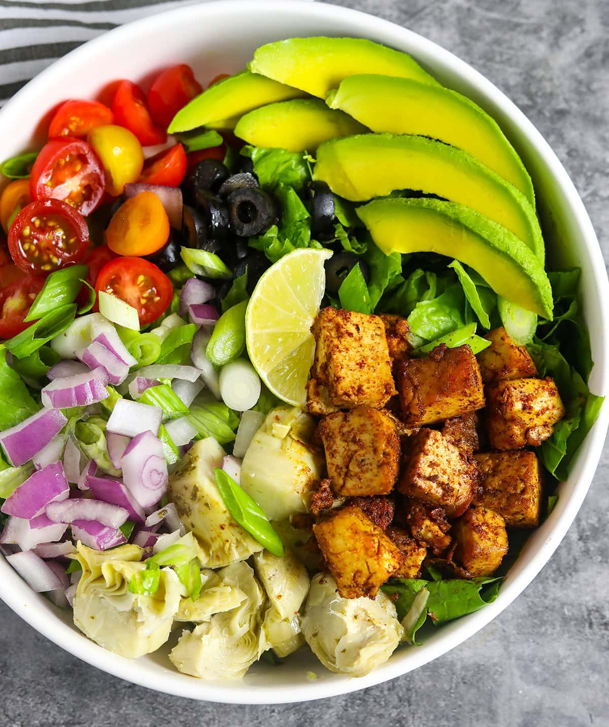 Overlay Cajun tofu salad in a white bowl with slices of avocado, tomato, red onion, marinated tofu, artichoke hearts, green onion, lettuce, olives in a white bowl on a grey background