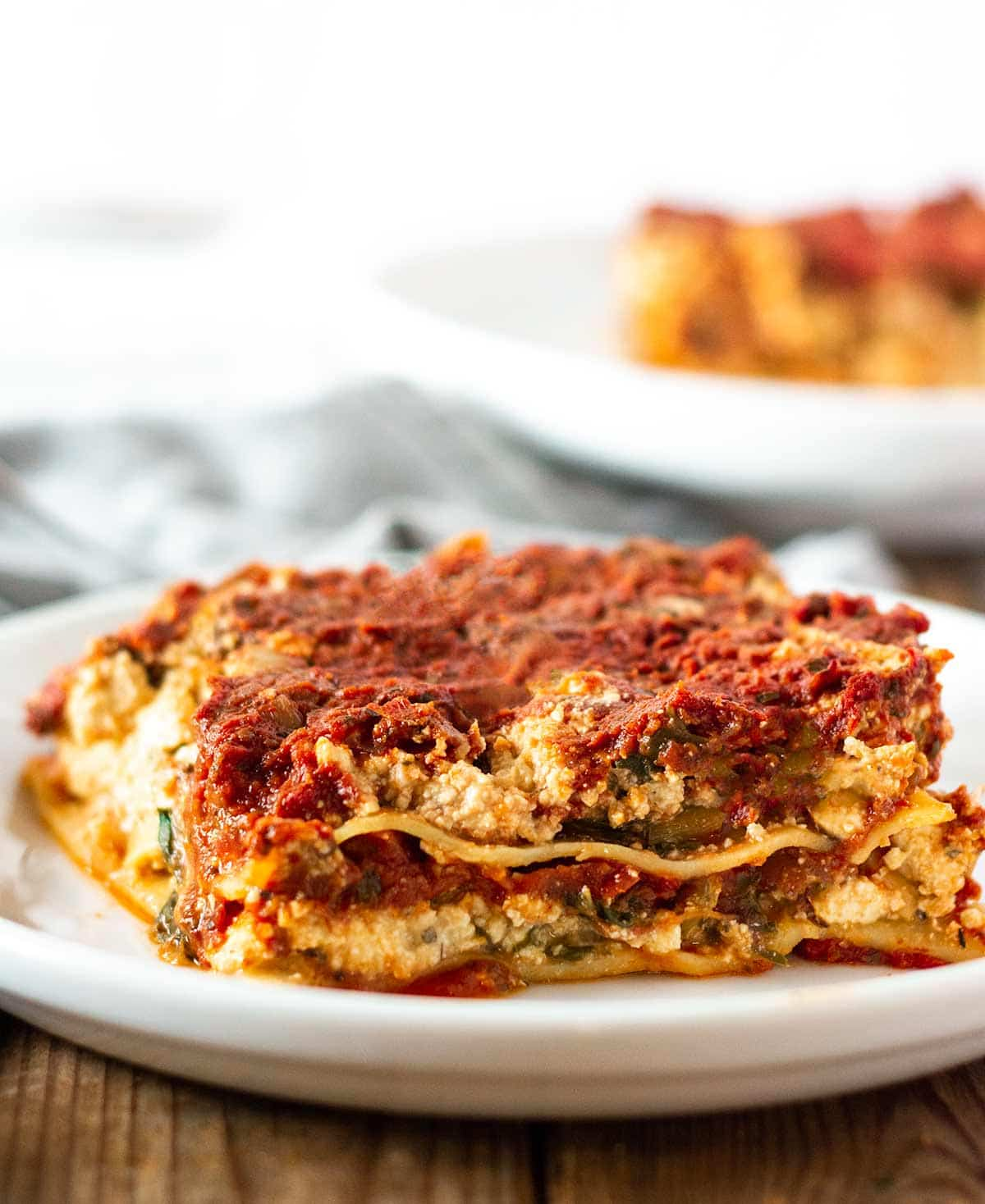 a slice of gluten free lasagna on a white plate