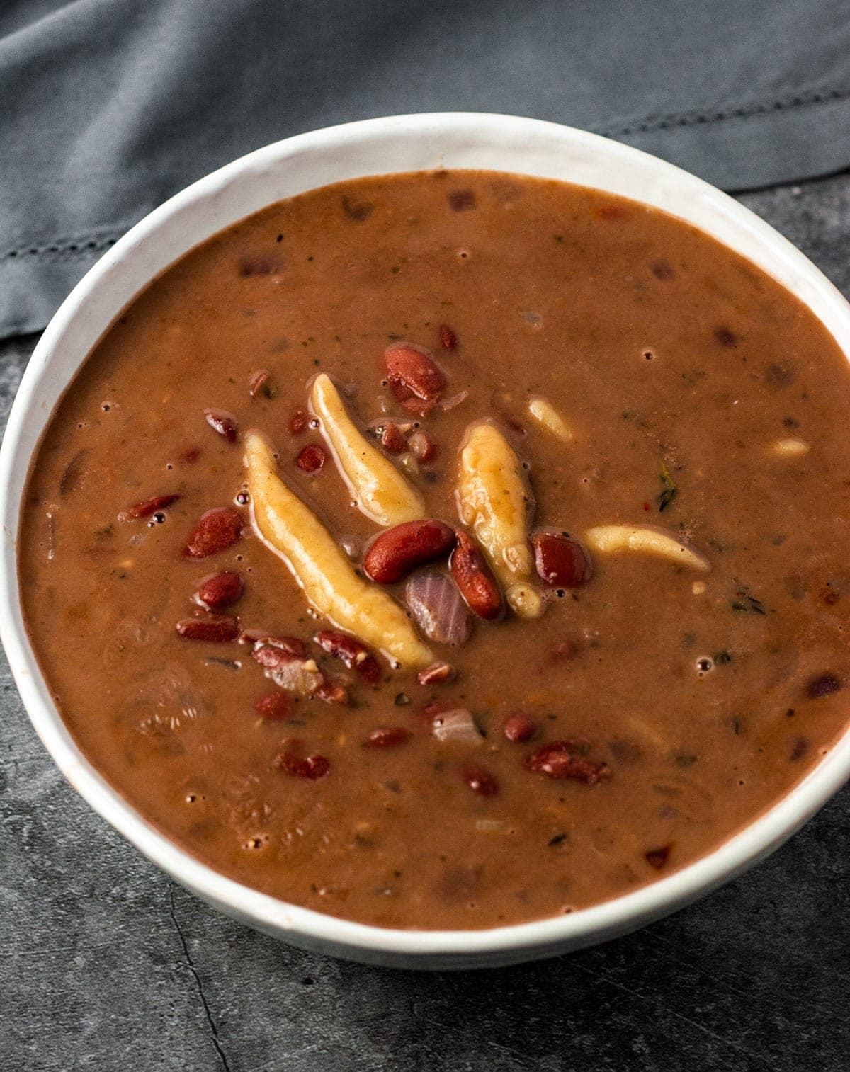Overlay Red peas soup with dumplings in a white bowl on a grey background