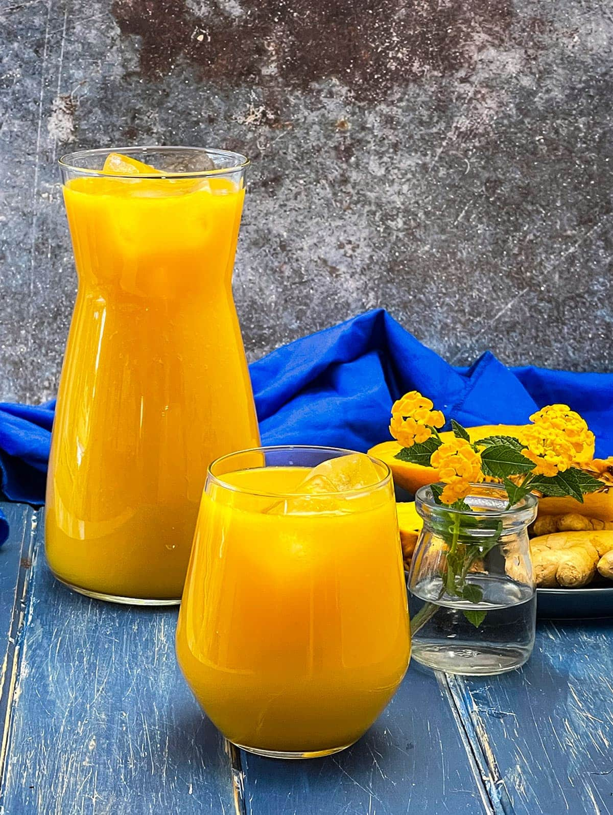 mango pineapple juice in a flask and glass on a blue wooden background with a blue napkin