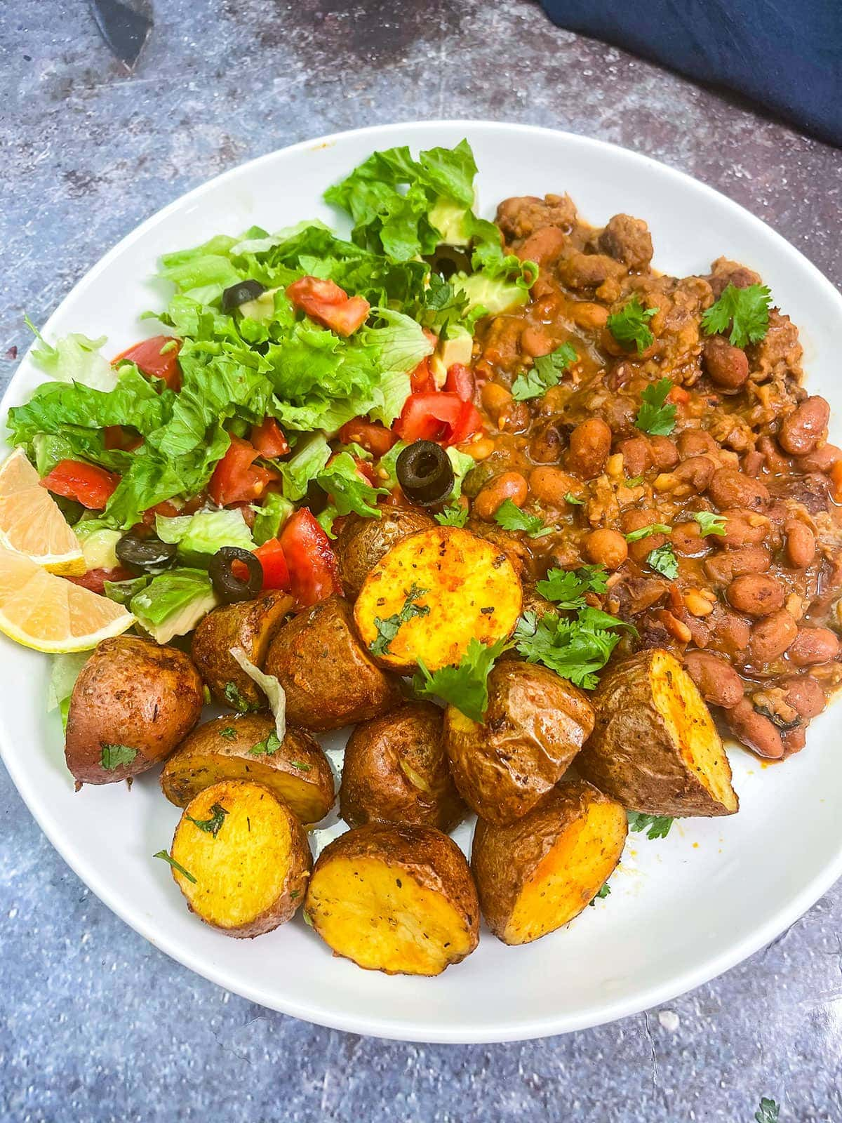 air fryer potatoes on a white plate with beans and salad