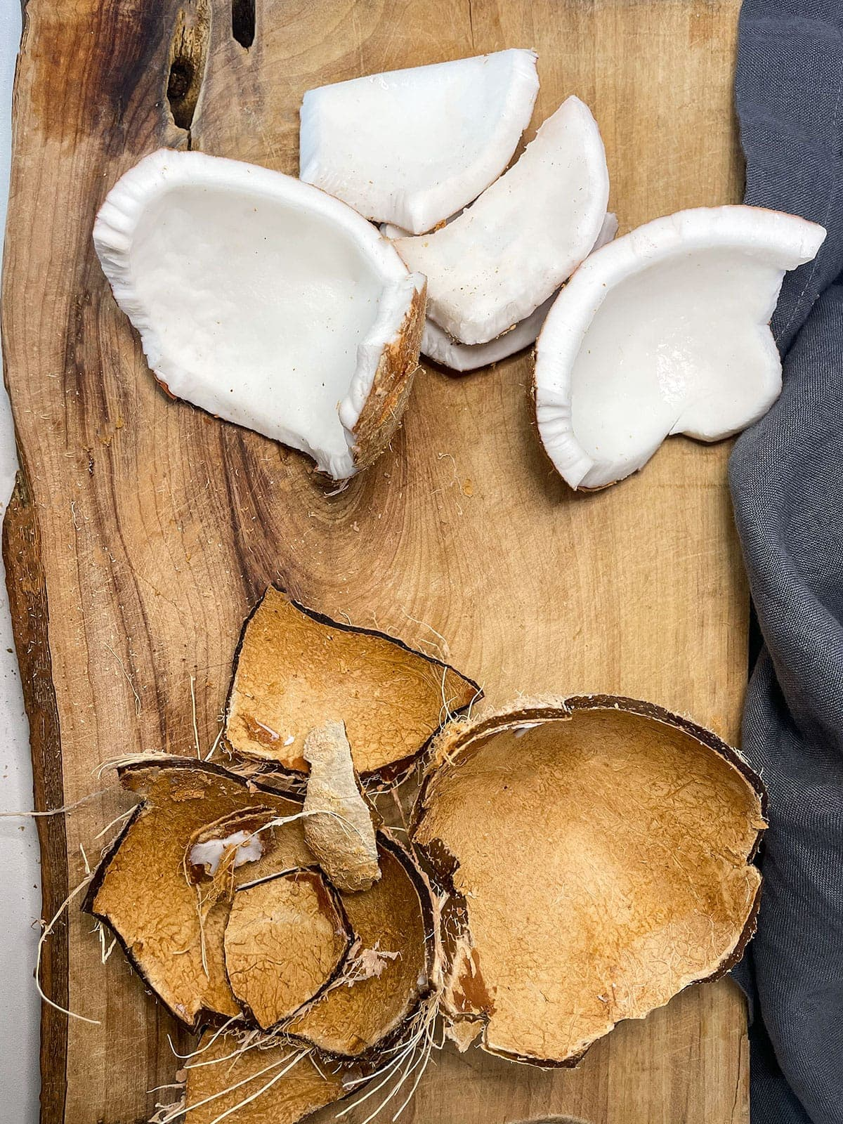removing coconut flesh from coconut shell on a wooden cutting board