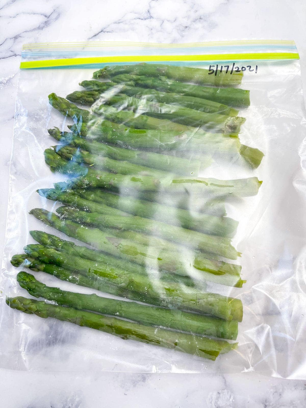 asparagus in a ziplock bag on a white marble background