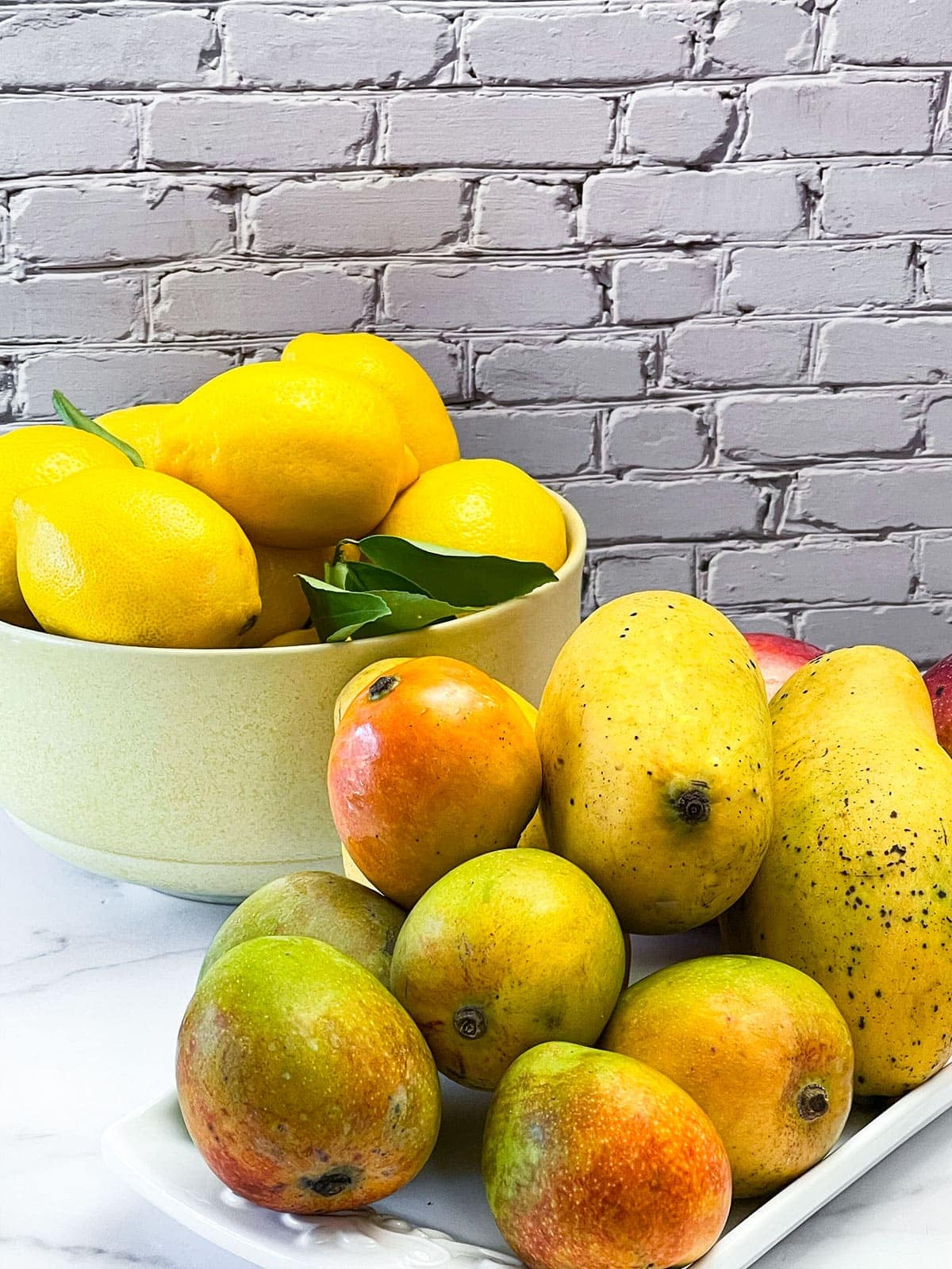 Mango lemonade ingredient, lemonade in a yellow bowl and mangoes on a white platter