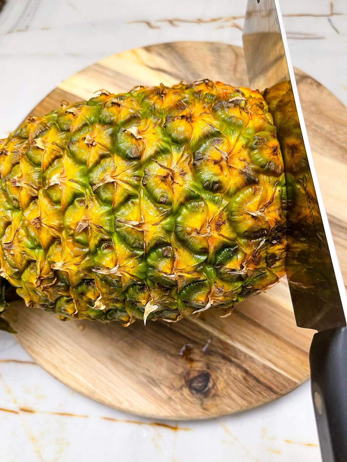 how to peel a pineapple, cutting the base off the pineapple with a knife