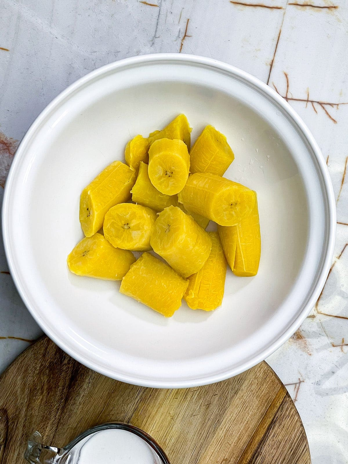 boiled plantains in a white bowl on a beige background