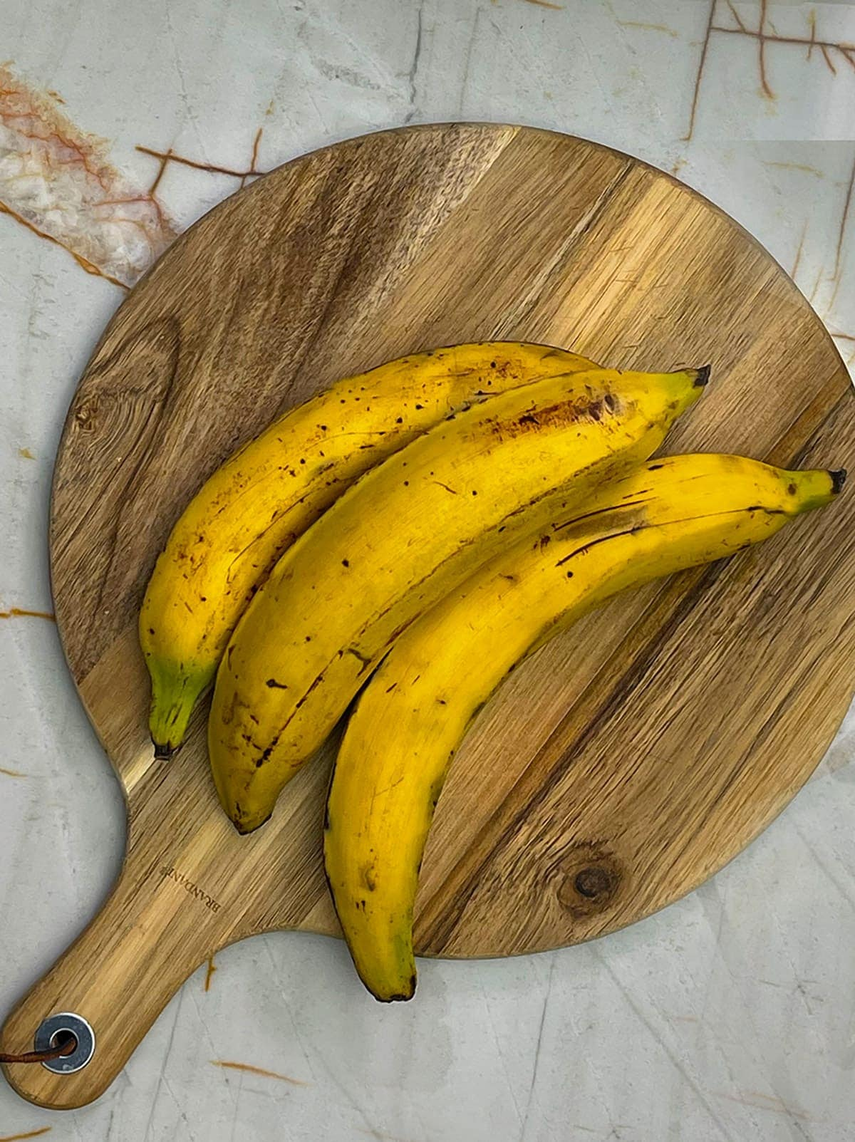 whole ripe plantains on cutting boad