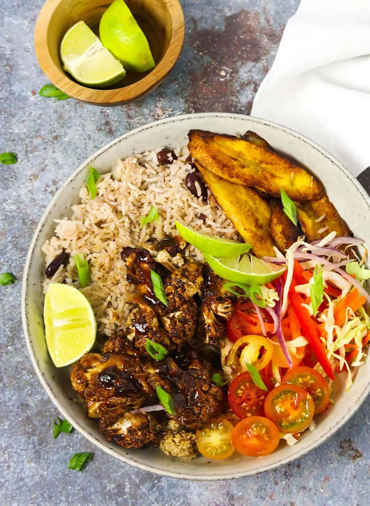 Overlay of bowl with jamaican jerk cauliflowerk rice, plantains on a grey background
