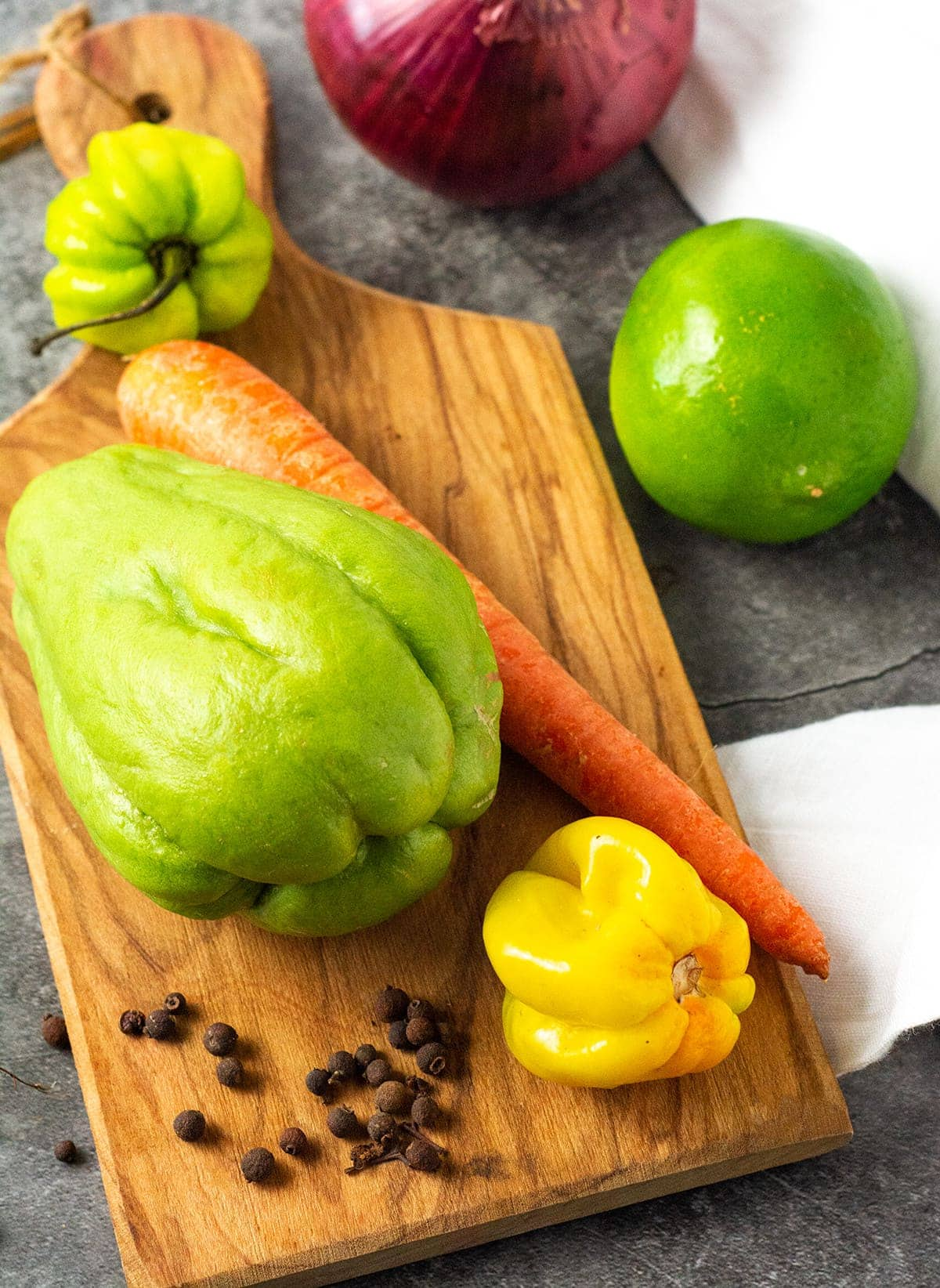 Carrot, chocho, onion, scotch bonnet pepper, pimento and lime on a cutting board on a grey background